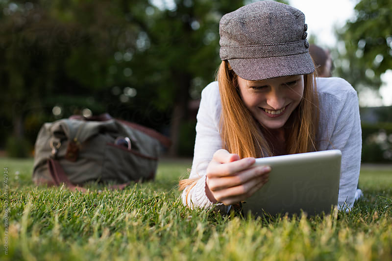 Beautiful young woman enjoying with her digital tablet at the park by michela ravasio for Stocksy United