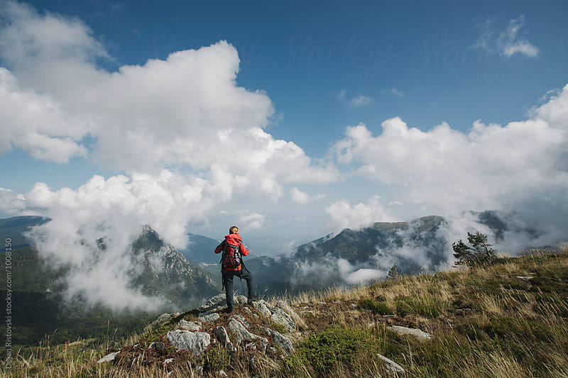 Woman hiker standing on a viewpoint. by Dejan Ristovski for Stocksy United