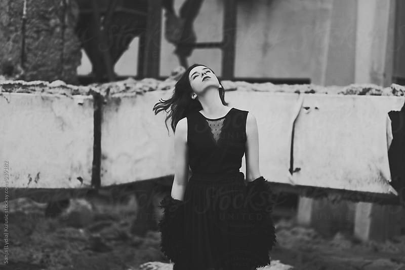 Girl in black day dreaming with wind in her hair by Sanja (Lydia) Kulusic for Stocksy United