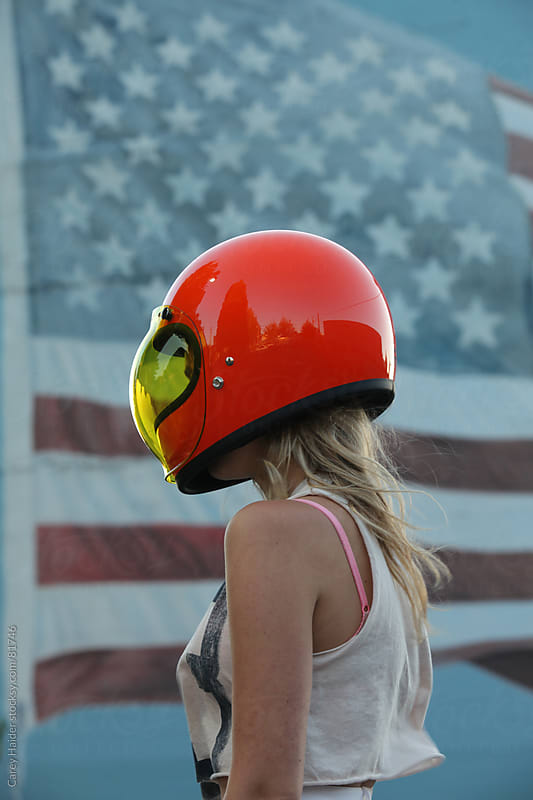 Americana Youthful Woman Wearing A Motorcycle Helmet Infront Of An American Flag by Carey Haider for Stocksy United