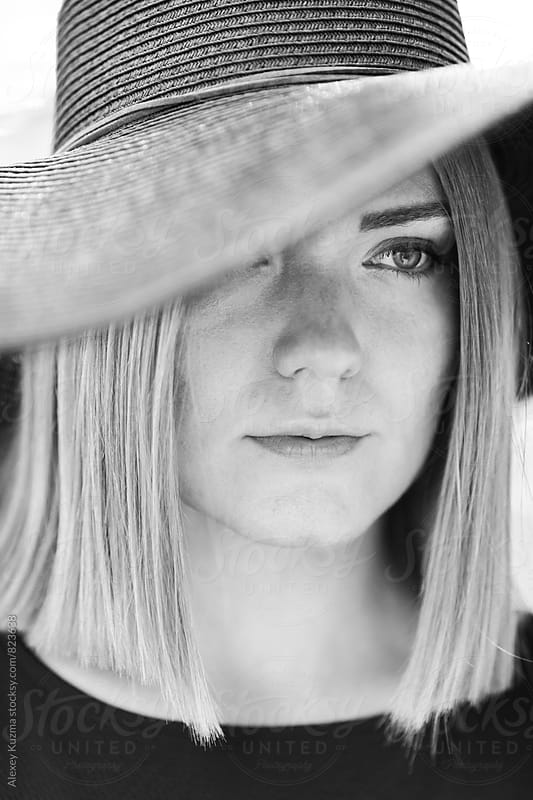 closeup of young blond woman with black hat by Alexey Kuzma for Stocksy United