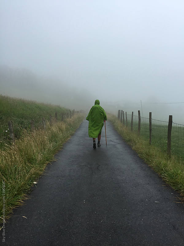 Back view of an hiker walking under the rain by Luca Pierro for Stocksy United