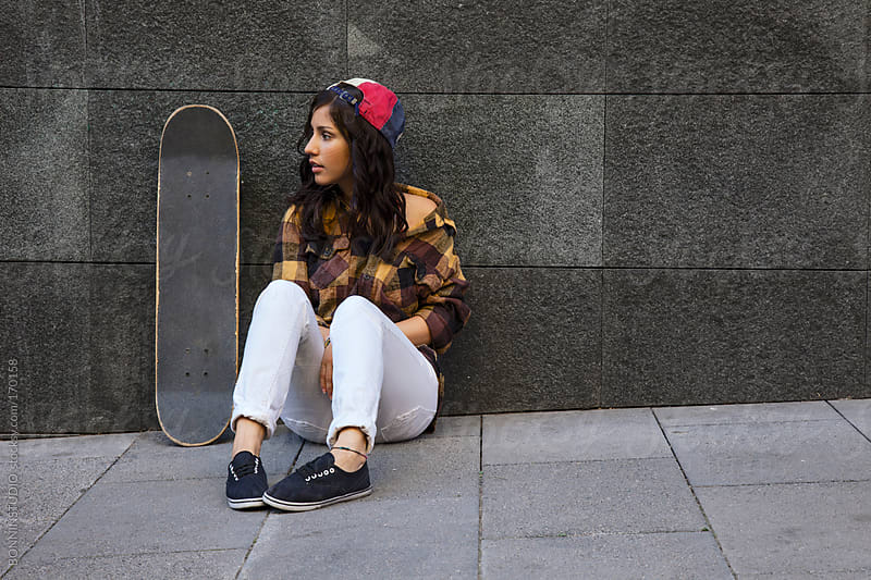 Young skater girl wearing colorful cap sitting on floor. by BONNINSTUDIO for Stocksy United