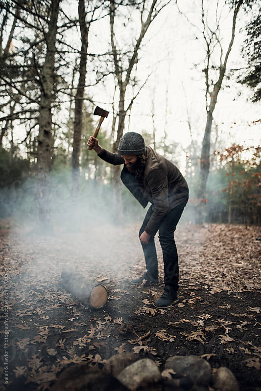 Man swinging axe to cut firewood by Isaiah & Taylor Photography for Stocksy United