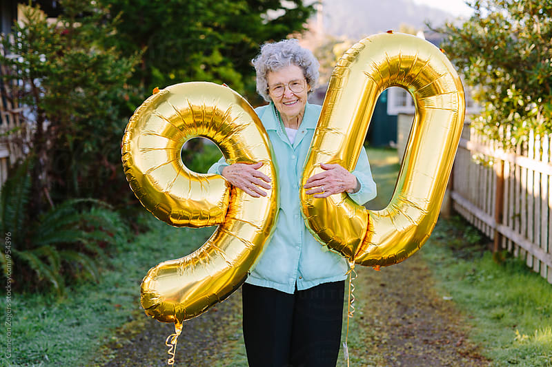 elderly woman holding number balloons for ninetieth birthday by Cameron Zegers for Stocksy United