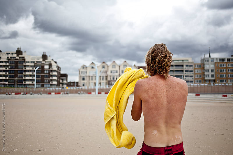 Young man comes back from swimming and walks back by Denni Van Huis for Stocksy United