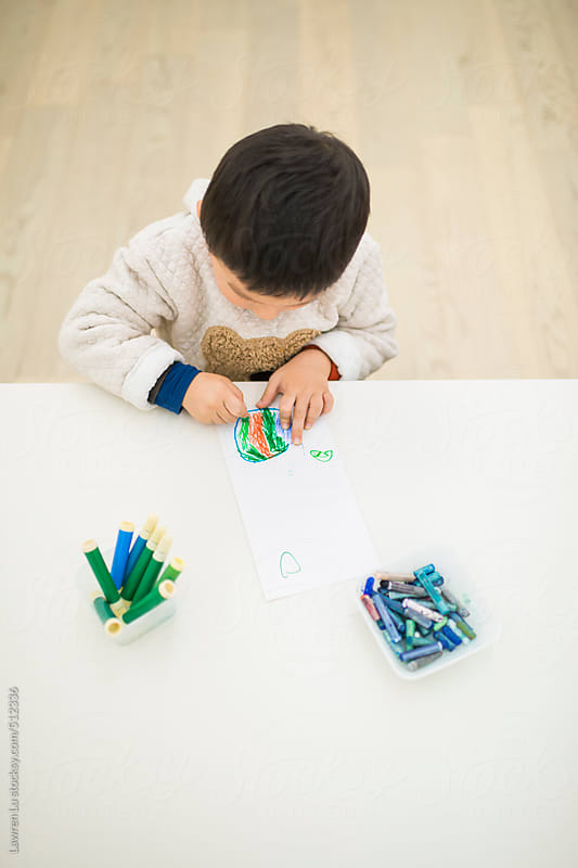 Cute Male Kid Coloring Paper with Crayons at White Table. by Lawren Lu for Stocksy United