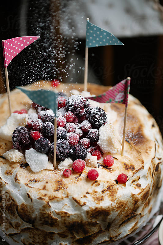 Italian meringue cake with summer fruits being dusted with icing sugar. by Darren Muir for Stocksy United