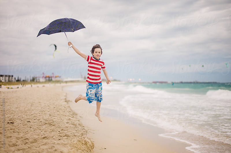 Boy jumping with an umbrella at the beach by Angela Lumsden for Stocksy United