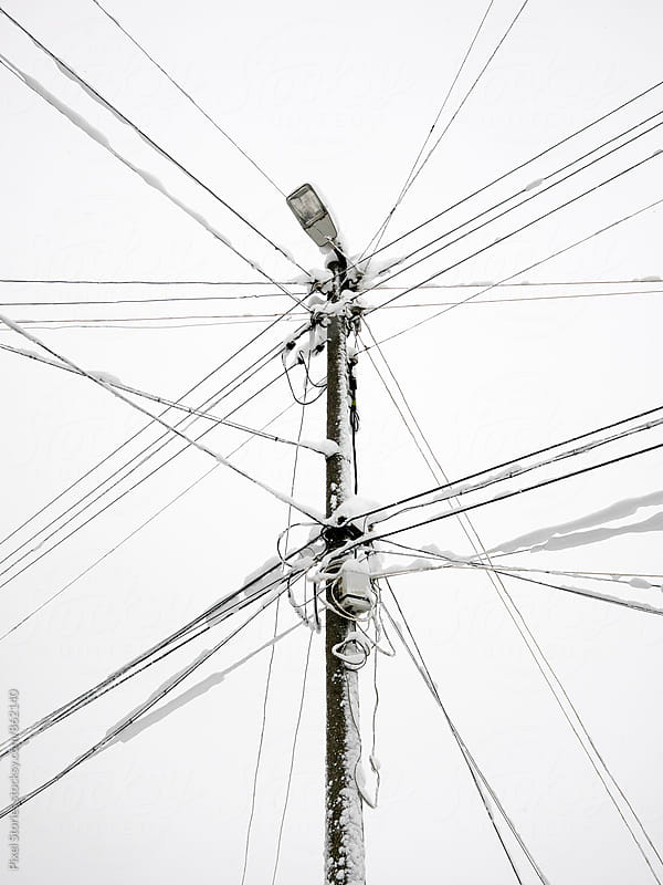 Lamppost with powerlines heavy with snow by Pixel Stories for Stocksy United