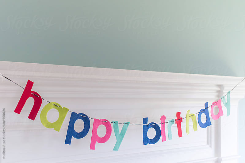 Mantel decorated with a happy birthday banner. by Melissa Ross for Stocksy United