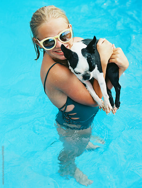 teenager with boston terrier in pool having fun by wendy laurel for Stocksy United