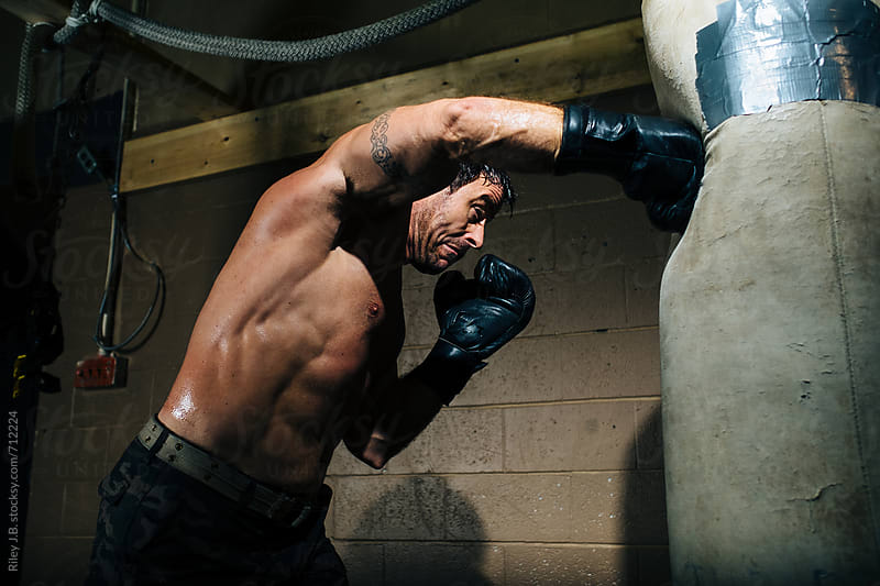 A boxer throws a hard punch at a punching bag in a gym by Riley J.B. for Stocksy United