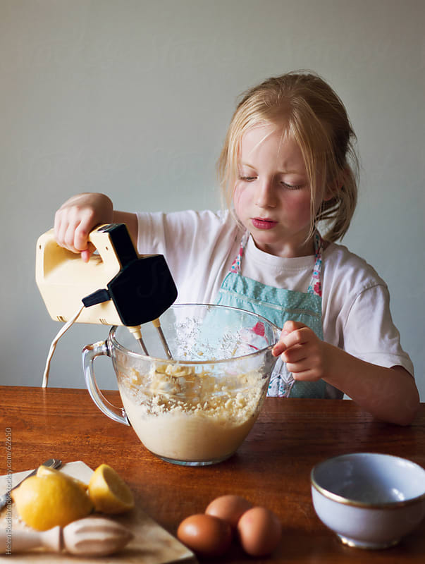 A little girl making Lemon Cake by Helen Rushbrook for Stocksy United