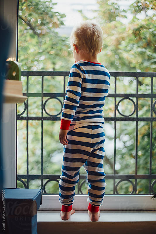 Boy in Striped Pajamas Looking Through The Window  by Lumina for Stocksy United