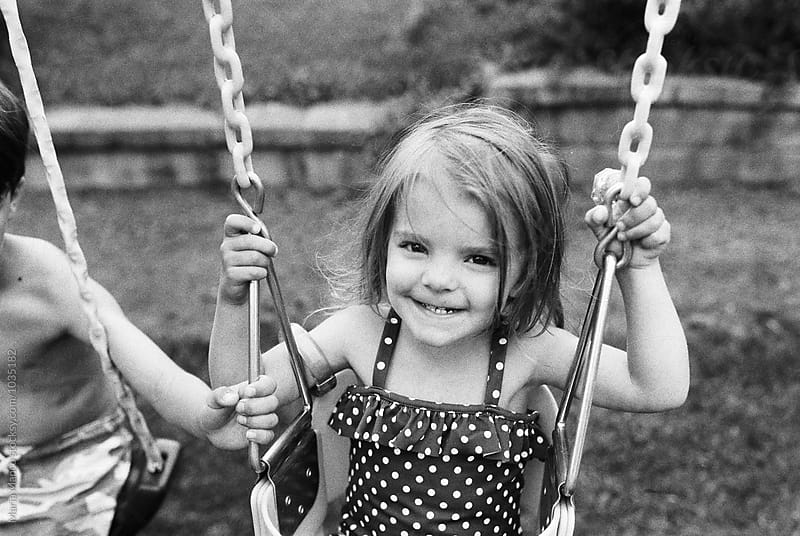 little girl smiling on swing by Maria Manco for Stocksy United