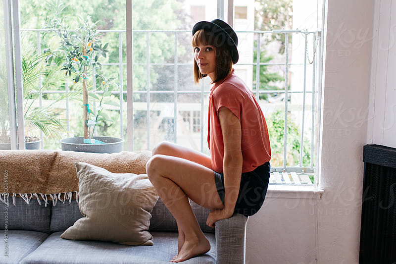young female woman sits on couch arm in apartment  by Jesse Morrow for Stocksy United