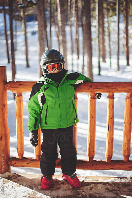 Boy dressed in ski clothes with helmet and googles by Angela Lumsden for Stocksy United