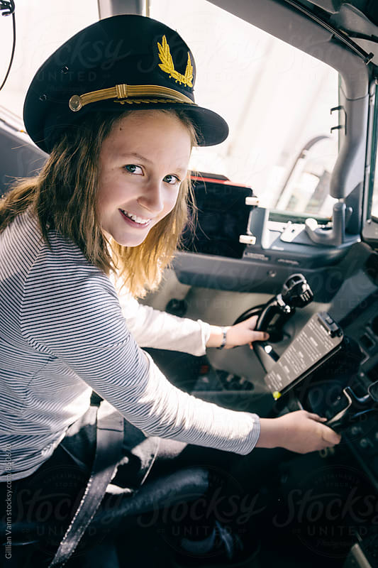 young girl excited about a trip to the cockpit of a plane by Gillian Vann for Stocksy United