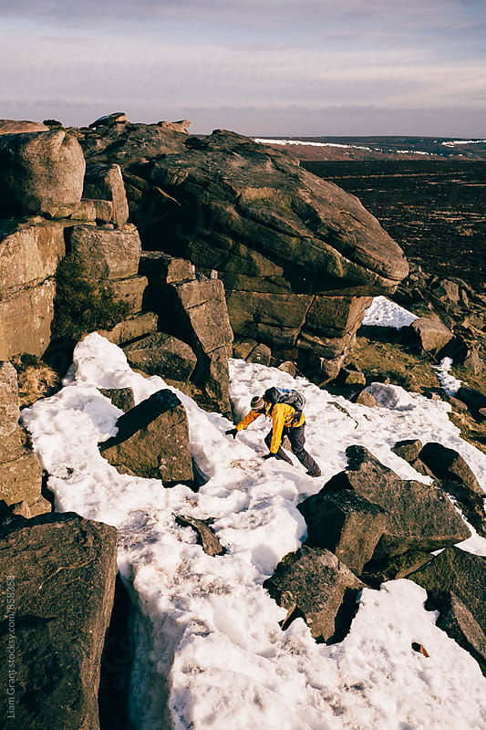 Male with backpack scrambling in the snow on Stanage Edge. Derbyshire, UK. by Liam Grant for Stocksy United