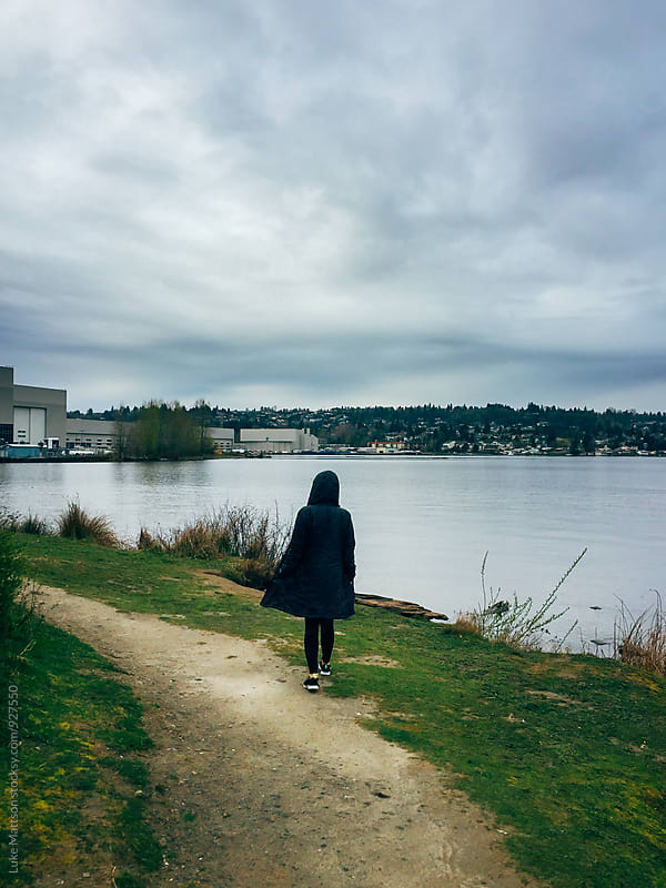 Woman In Black Rain Coat Walking Along Urban Lake Shore by Luke Mattson for Stocksy United
