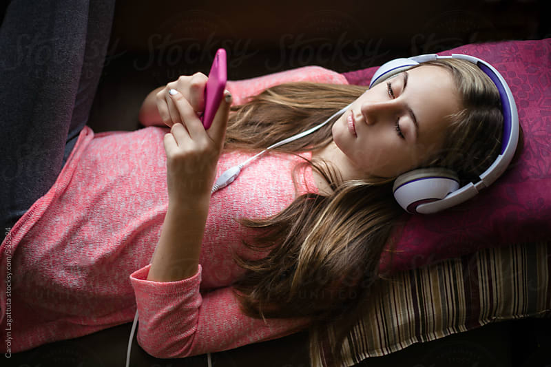 Teenage girl relaxing and  listening to music at home by Carolyn Lagattuta for Stocksy United