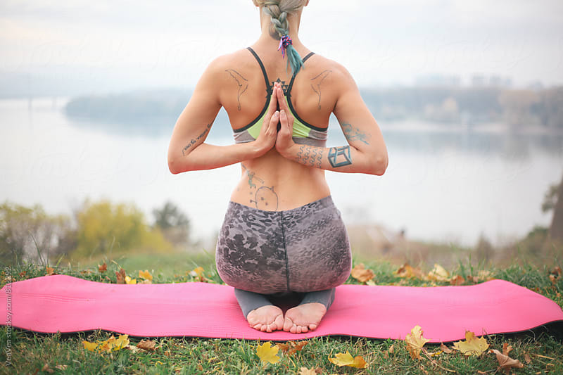 Handsome tattooed woman doing yoga outdoors by Marija Mandic for Stocksy United