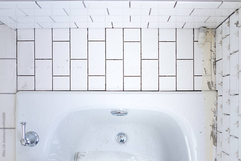A newly tiled bathtub surround awaiting grout by Riley J.B. for Stocksy United