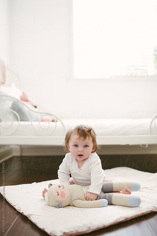 cute Baby sitting with lamb doll on floor by Kristin Rogers Photography for Stocksy United