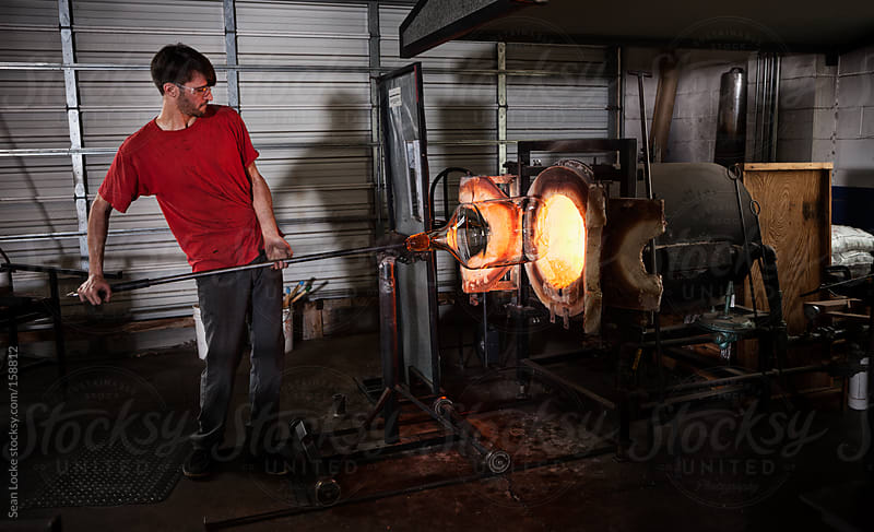 Glass: Man Lifts Heavy Final Piece Into Yoke to Reheat by Sean Locke for Stocksy United