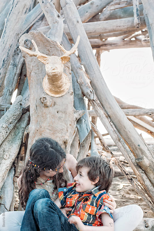 Siblings talking and laughing with each other on the Beach at Sunset by Beatrix Boros for Stocksy United