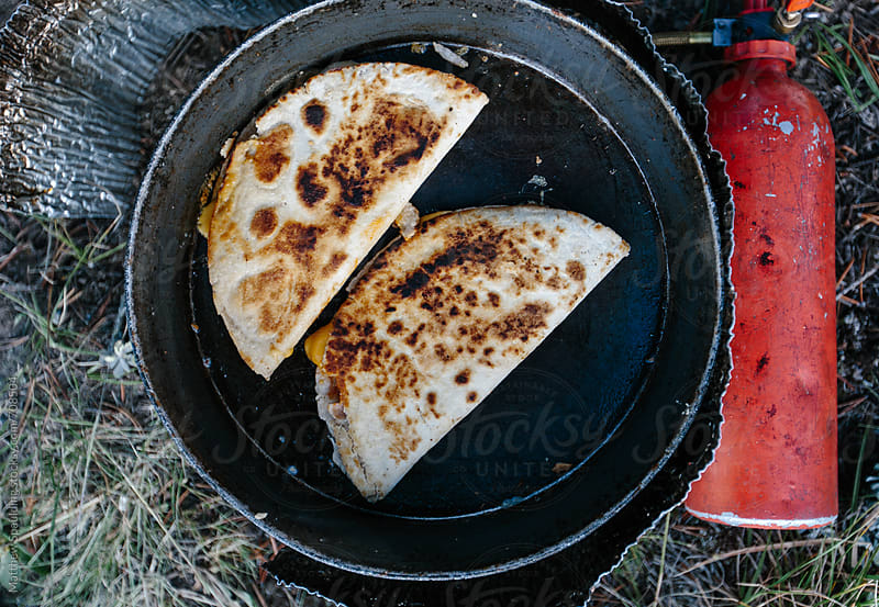 Quesadillas cooking on camping stove outdoors by Matthew Spaulding for Stocksy United