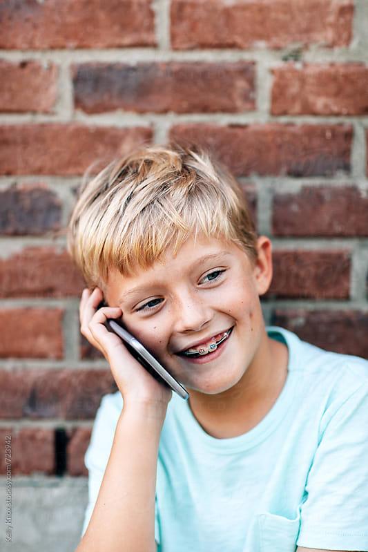boy laughing while talking on a phone by Kelly Knox for Stocksy United