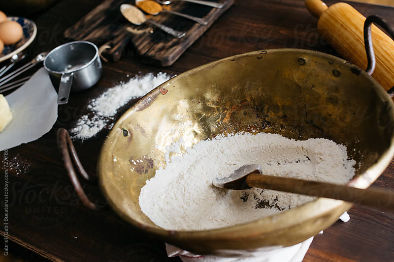 Old brass mixing bowl with flour by Gabriel (Gabi) Bucataru for Stocksy United