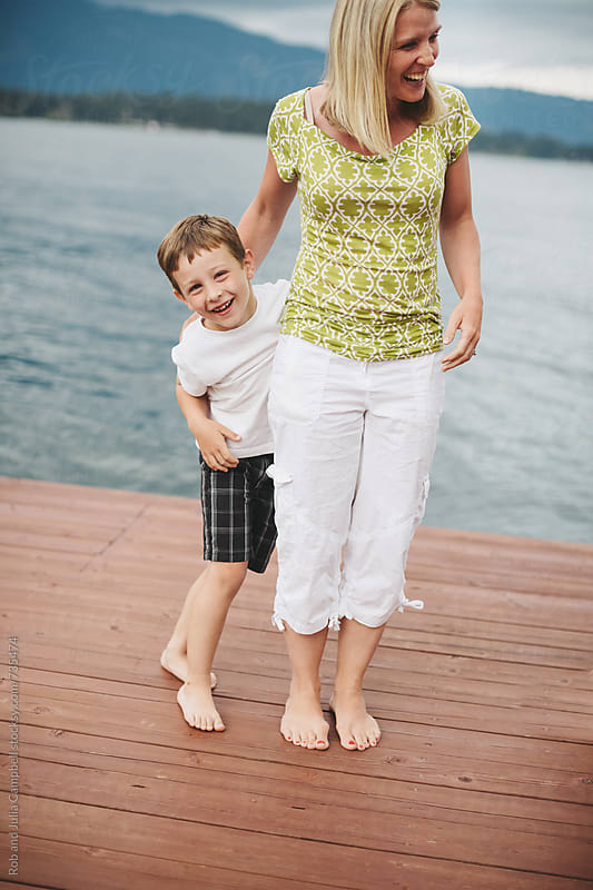Mom and son laughing on lake dock by Rob and Julia Campbell for Stocksy United