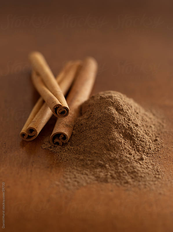 Cinnamon sticks and ground cinnamon by Daniel Hurst for Stocksy United