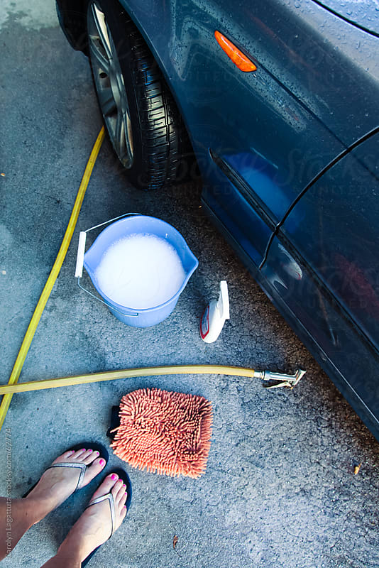 Female washing her own car at home - do it yourself by Carolyn Lagattuta for Stocksy United