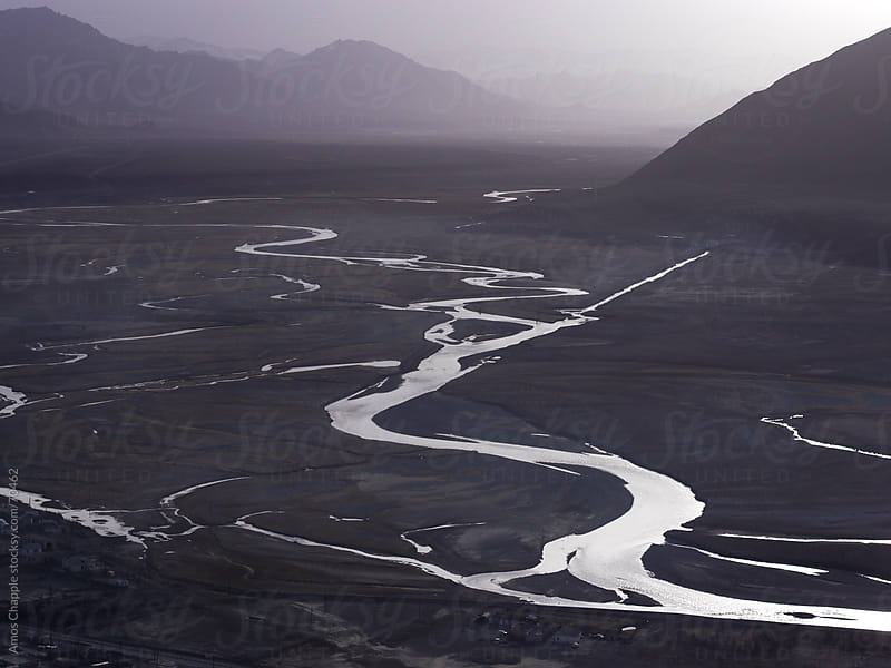 A river snakes across an alpine plain near Murghab.  by Amos Chapple for Stocksy United