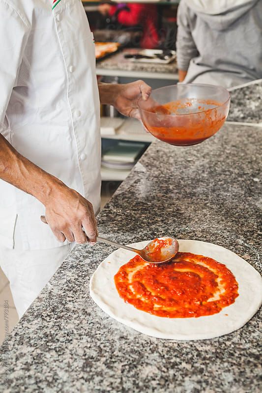 Pouring Tomato Sauce on the Raw Dough of a Pizza by Giorgio Magini for Stocksy United