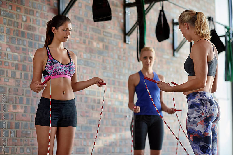 Fitness trainer showing teaching how to hold skipping ropes  by Daxiao Productions for Stocksy United