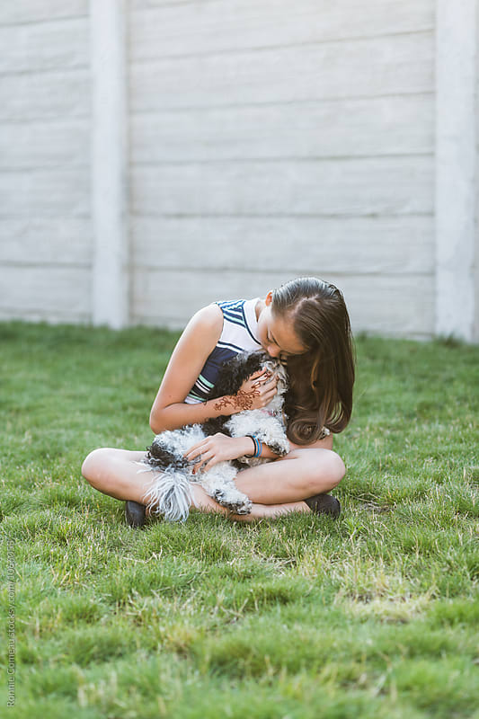 Teen Girl Hugging Her Dog by Ronnie Comeau for Stocksy United