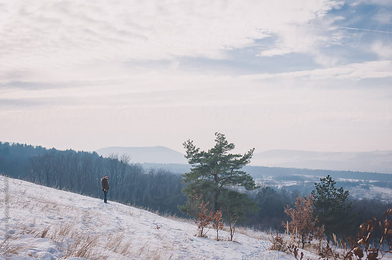 Winter landscape with a man viewing the beautiful scenery by Lea Csontos for Stocksy United