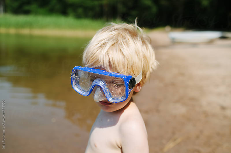Blonde boy in oversized blue goggles on a beach with a forest in the background. by Julia Forsman for Stocksy United