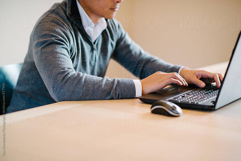 asian man types on laptop computer  by Tara Romasanta for Stocksy United