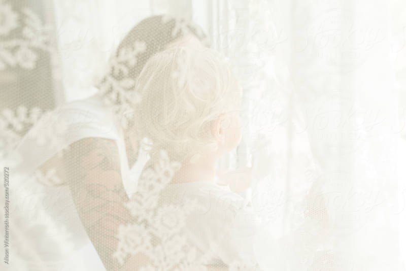 Mother And Son Look Through The Curtains by Alison Winterroth for Stocksy United