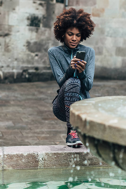 Young afro woman using phone after running on the street.  by BONNINSTUDIO for Stocksy United
