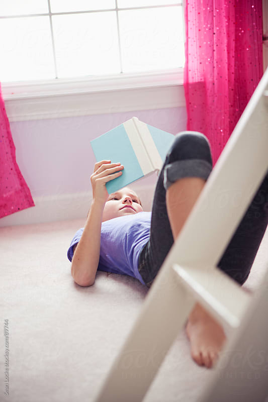 Girl: Young Girl Reads Book in Bedroom by Sean Locke for Stocksy United