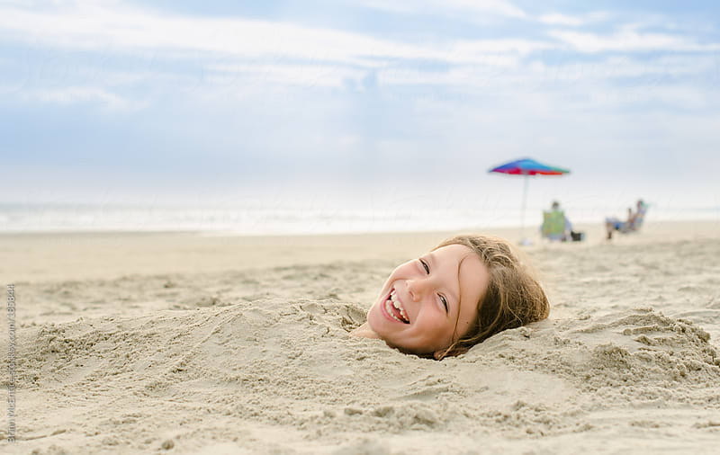 Laughing Girl Buried in Sand at Beach by Brian McEntire for Stocksy United