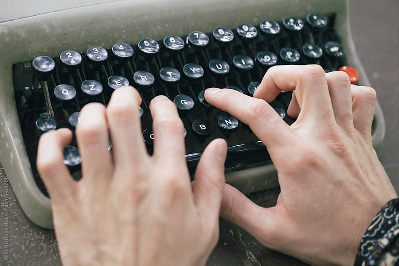 Man working on a typewriter in the garden by Alberto Bogo for Stocksy United