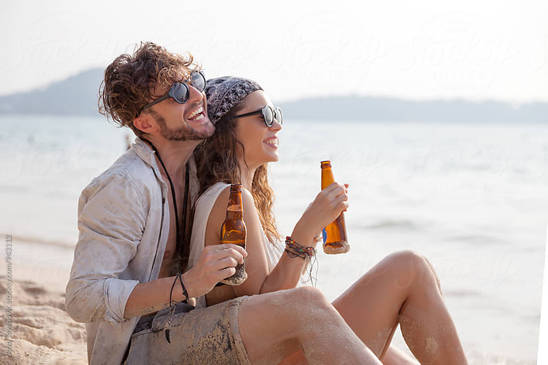 Couple enjoying their holiday drinking beer at the beach by Jovo Jovanovic for Stocksy United